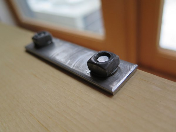 The hinges are bolted through the lid and secured with square nuts.