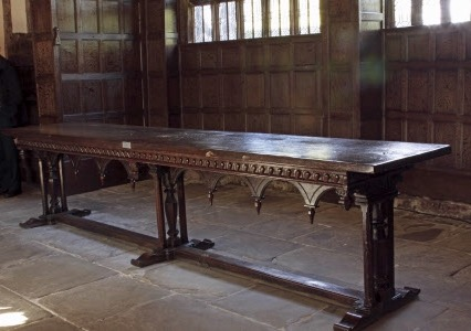 Oak refectory table, the top being original (possibly late 15th century), the frame of late 18th or 19th century date and having a round arcade with bosses below the spandrels. The top is mounted on three supports with a single stretcher running lengthways (appearing to be a later addition). The top of the frame has six pendant bosses at regular intervals carved with Ionic capitals.